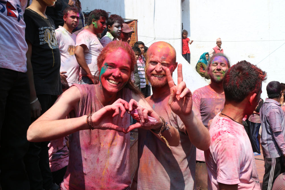 Both signs do make friends - travelers enjoying holi festival in Nepal
