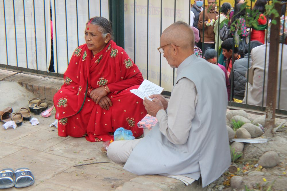 A  senior citizen probably wants to know the future of her family - astrologer are common outside temples in Nepal
