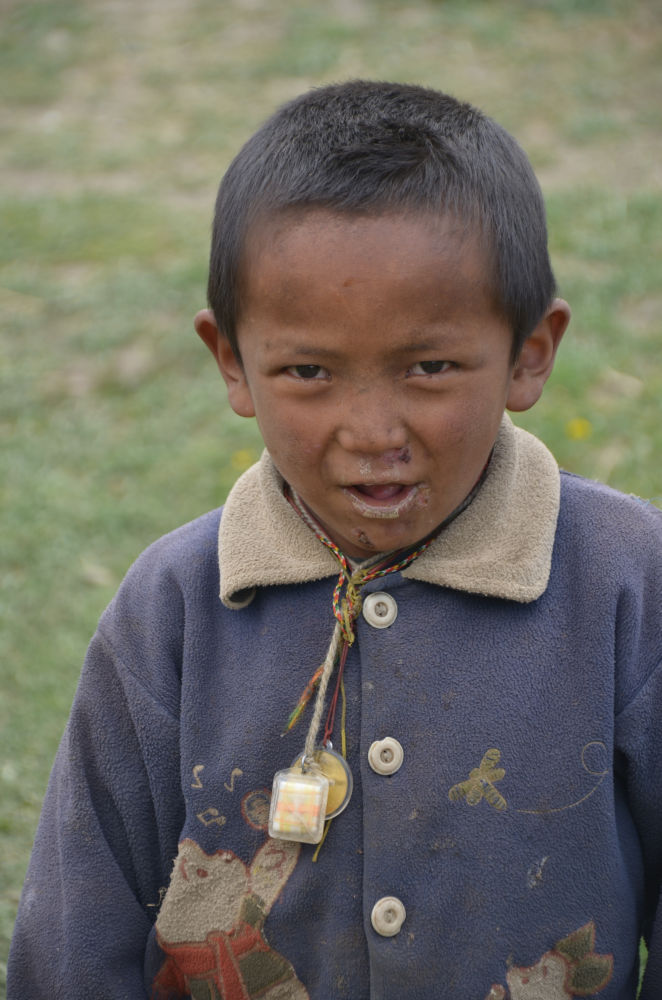 A smart kid's mischievous look in Dolpo
