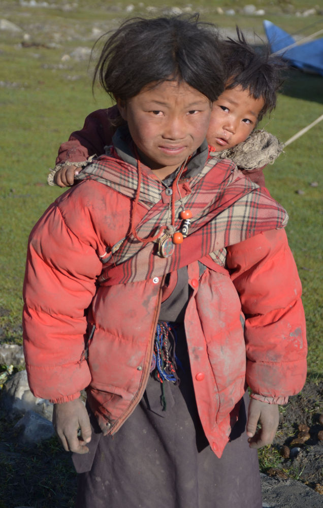 Young little girl parenting her infant sibling in Dolpa