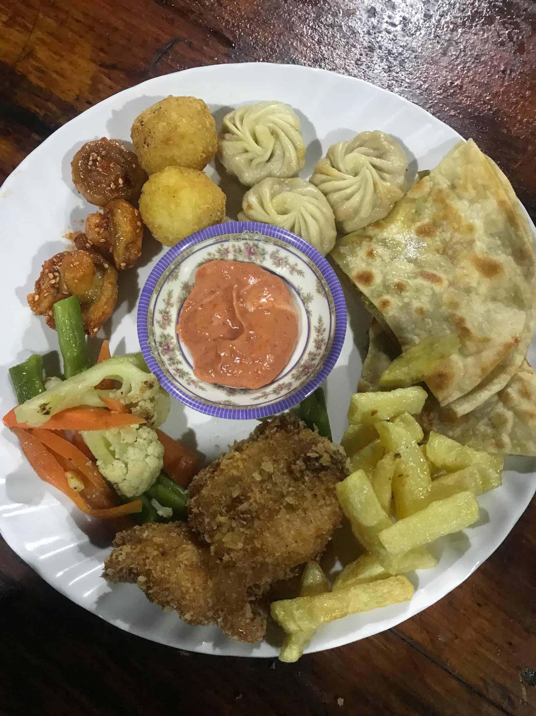 A Lunch Platter of bread, fries, fried chicken, boiled vegetables, fried mushroom, cheese balls and momo Everest Base Camp Trek